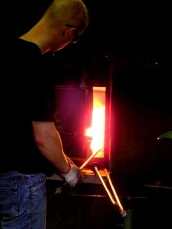 Glass artist Eero Vaikre removes glass from the oven