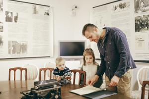 A father with two children by the table where Tartu Peace Treaty was signed
